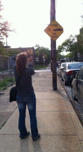 """Esther taking a picture of a street sign that says """"Share the Road"""""""