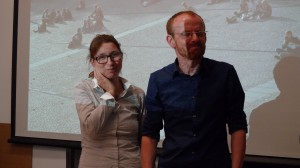 Esther and Ivar stand in front of a projection of one of their past works...